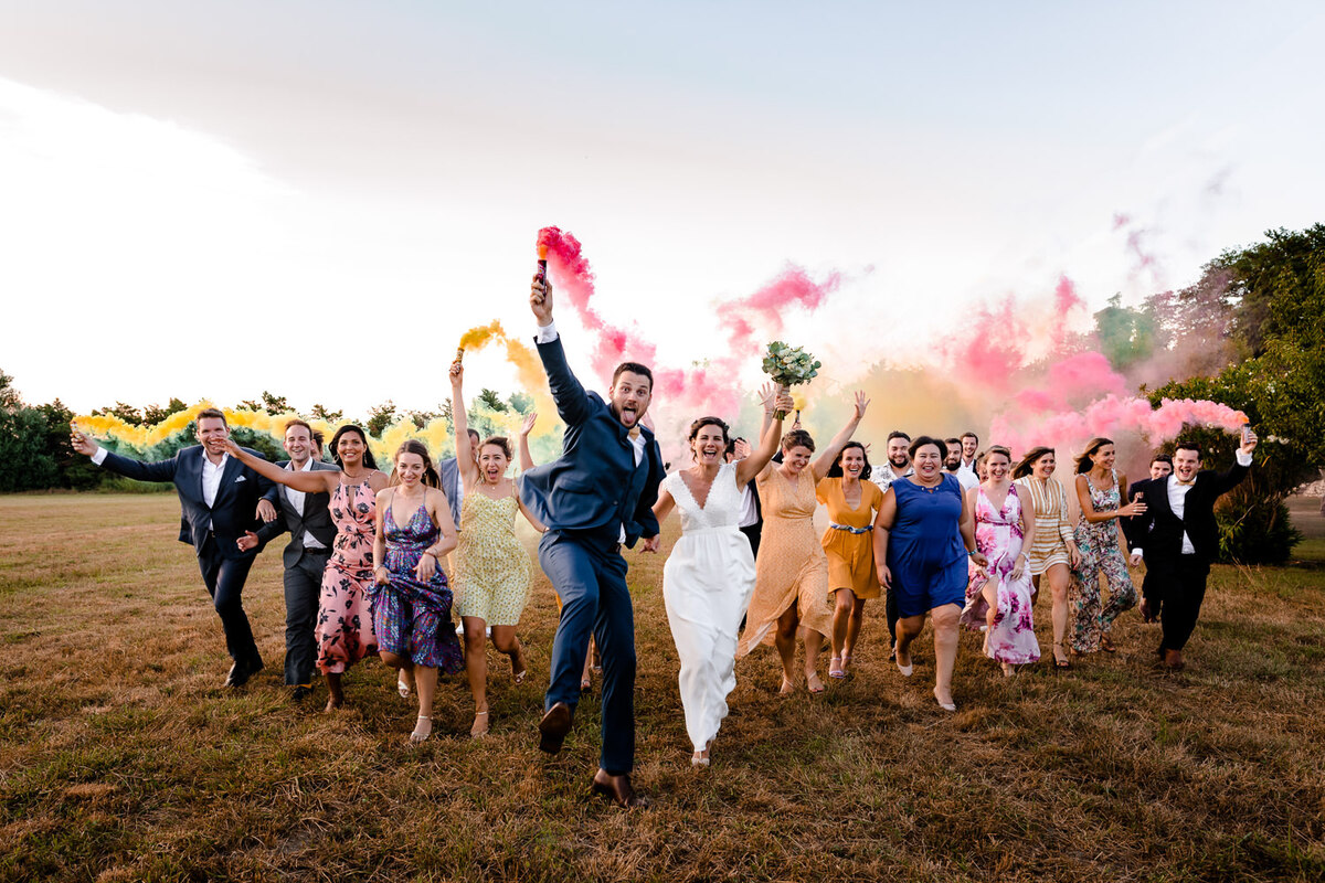 Photo de groupe avec des fumigènes lors d'un mariage à Millau
